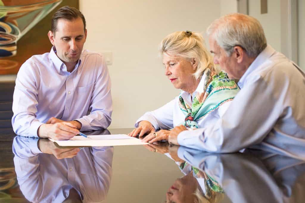 estate planning attorney signing documents with clients
